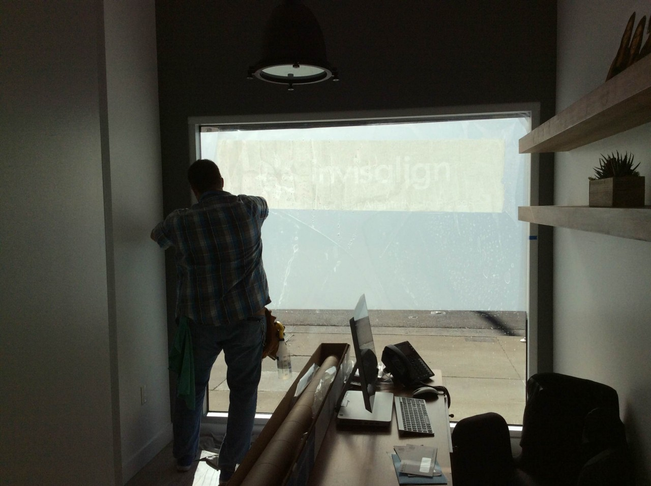 The custom cut window film is first applied at eye leveled. Then positioned into place on the dentists office window.